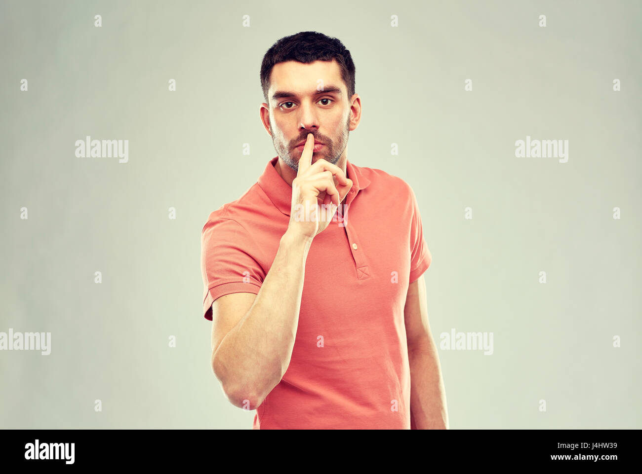 young man making hush sign over gray background - Stock Image