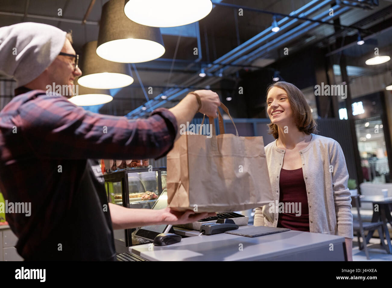 seller giving paper bag to customer at vegan cafe - Stock Image