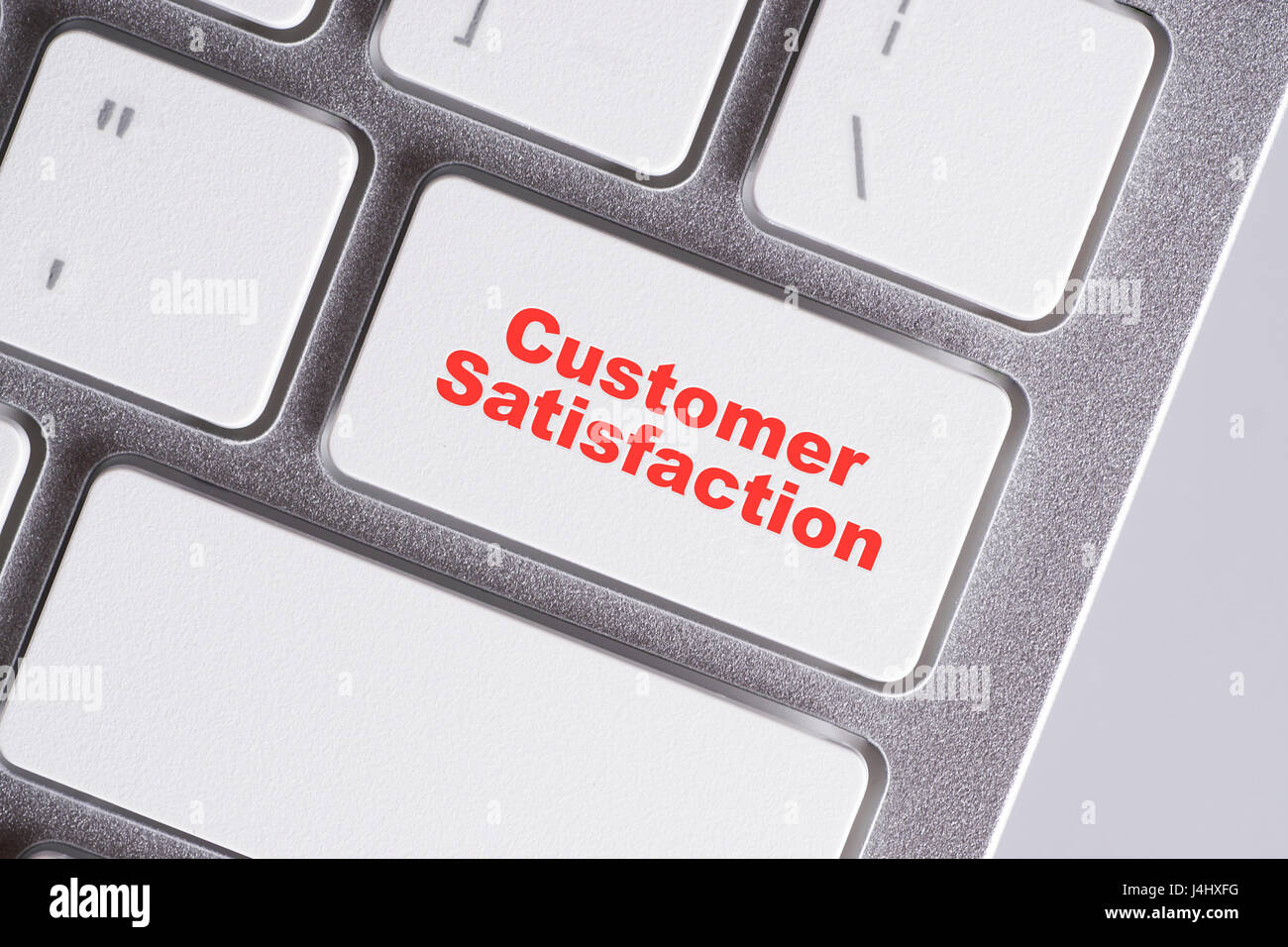 'Customer Satisfaction' red words on white keyboard - online, education and business concept - Stock Image
