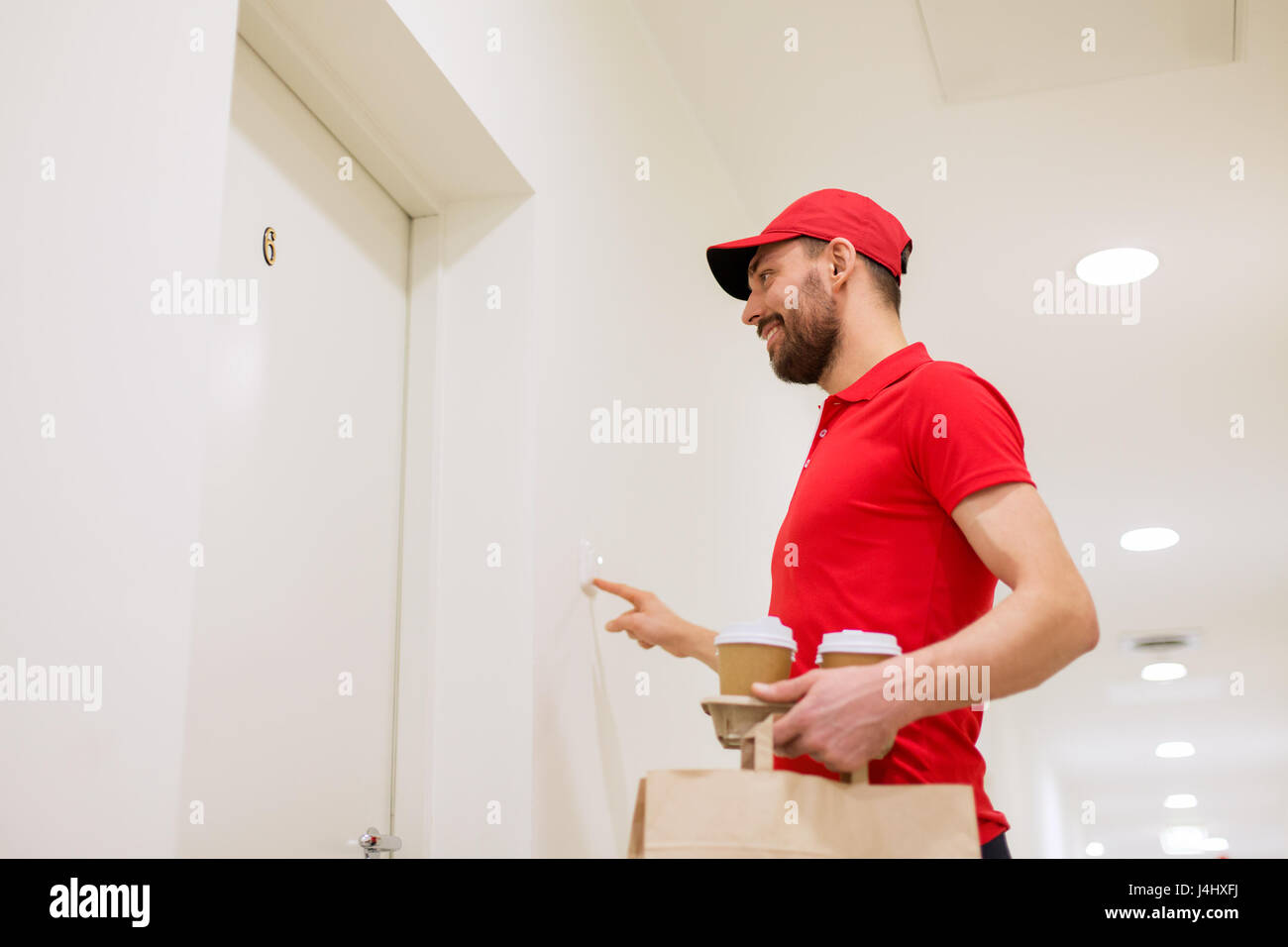 delivery man with coffee and food ringing doorbell - Stock Image