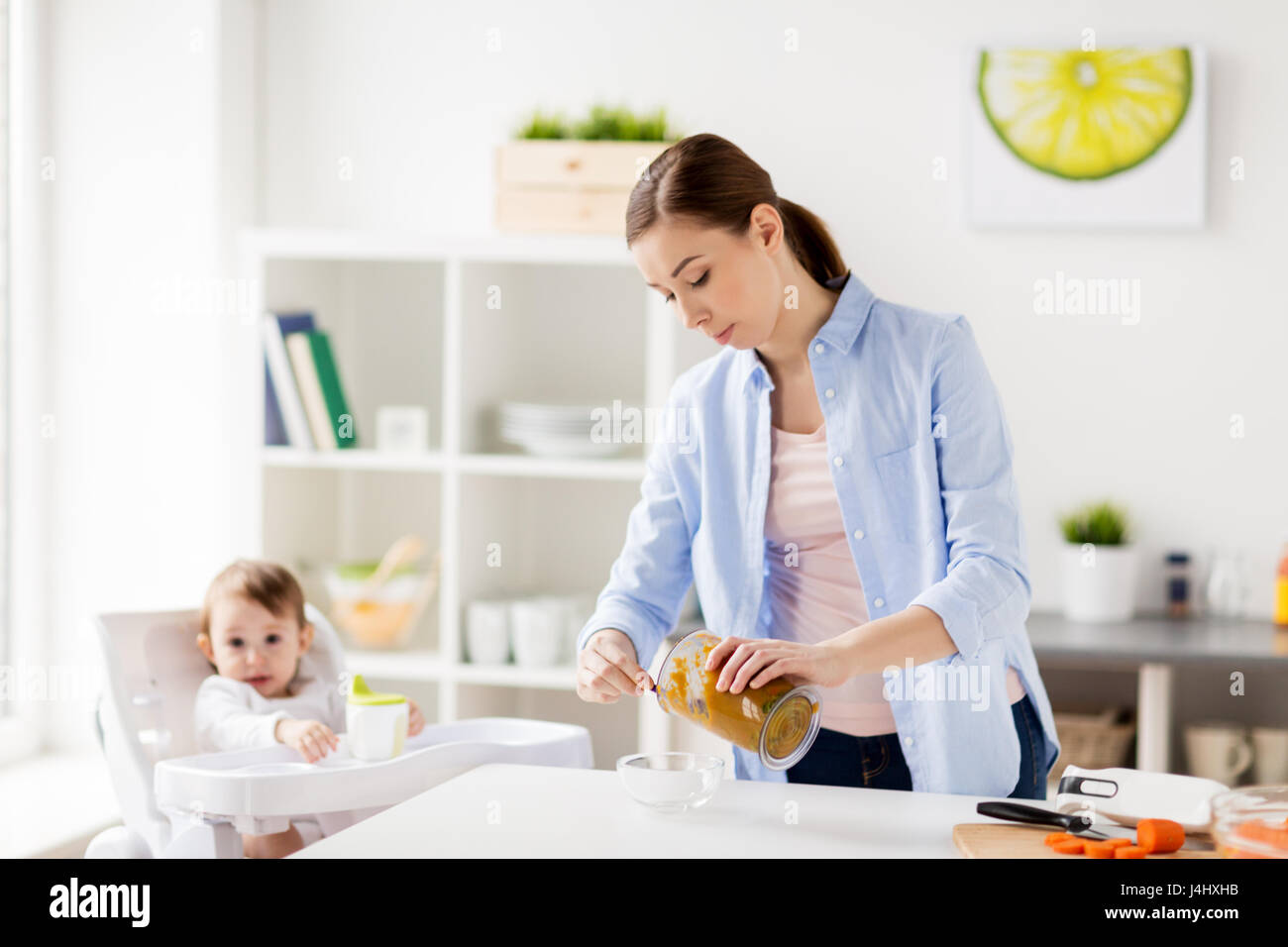 mother with blender cooking baby food at home - Stock Image