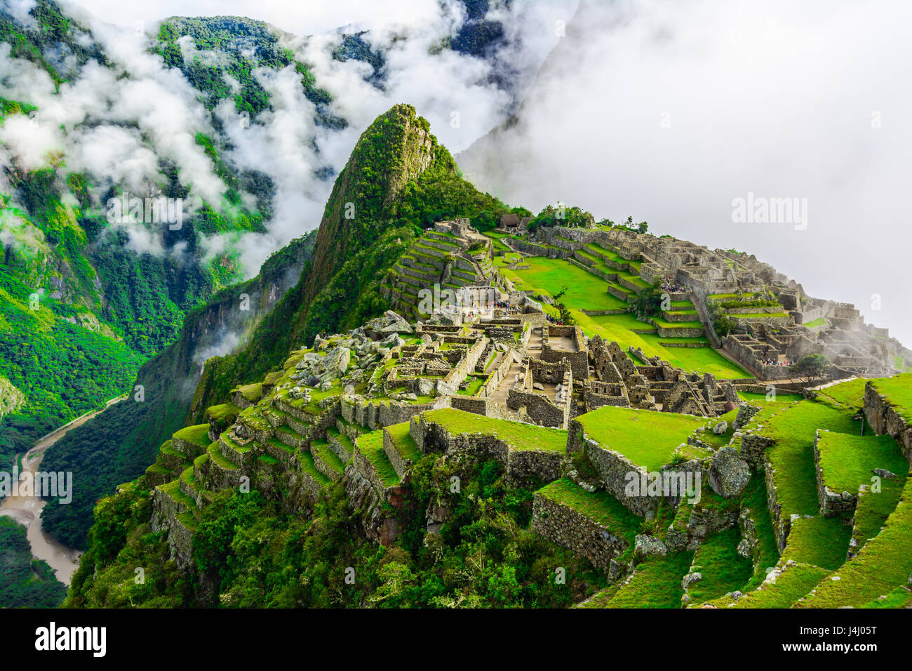 Overview of Machu Picchu, agriculture terraces, Wayna Picchu and surrounding mountains in the background - Stock Image