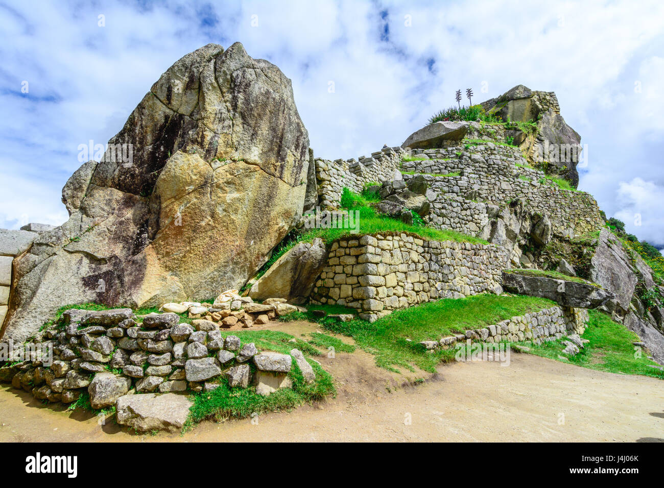 Sacred plaza and the hill with intiwatana observatory rock - Stock Image