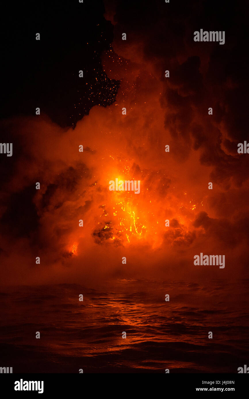 hot lava from from Kilauea Volcano creates steam explosions where it enters the ocean at Kamokuna in Hawaii Volcanoes - Stock Image