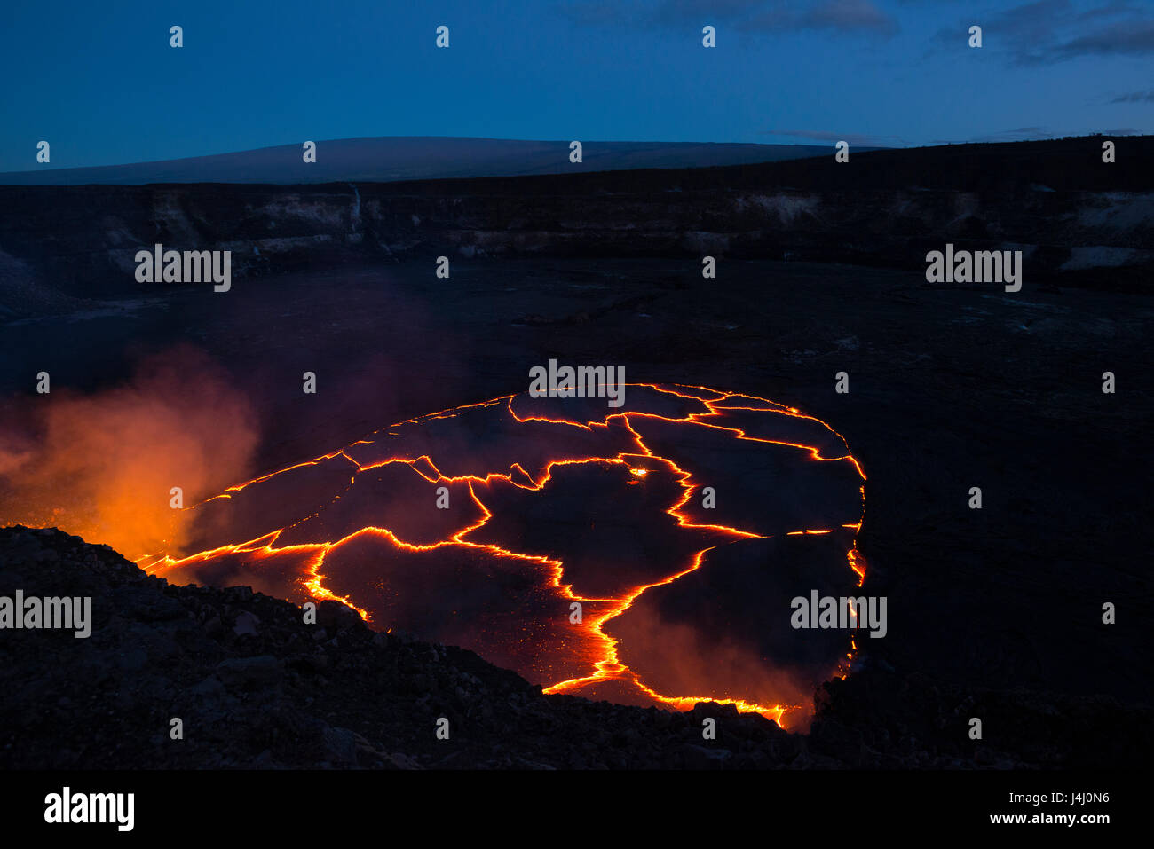 lava lake in caldera of Halemaumau Crater, Kilauea Volcano, Hawaii, USA, with Mauna Loa mountain in background in - Stock Image