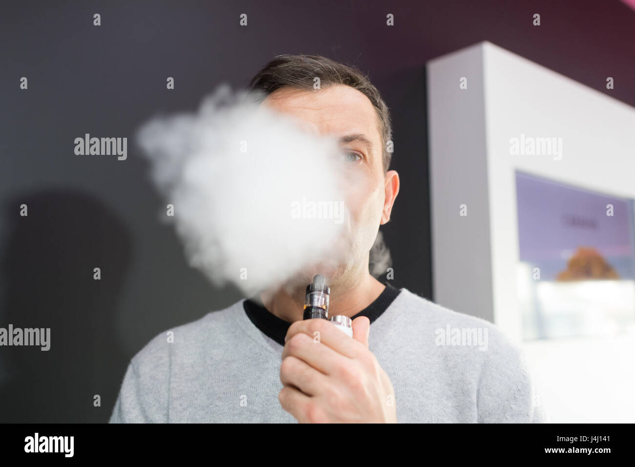 man obscured behind a cloud of vaporizer smoke - Stock Image