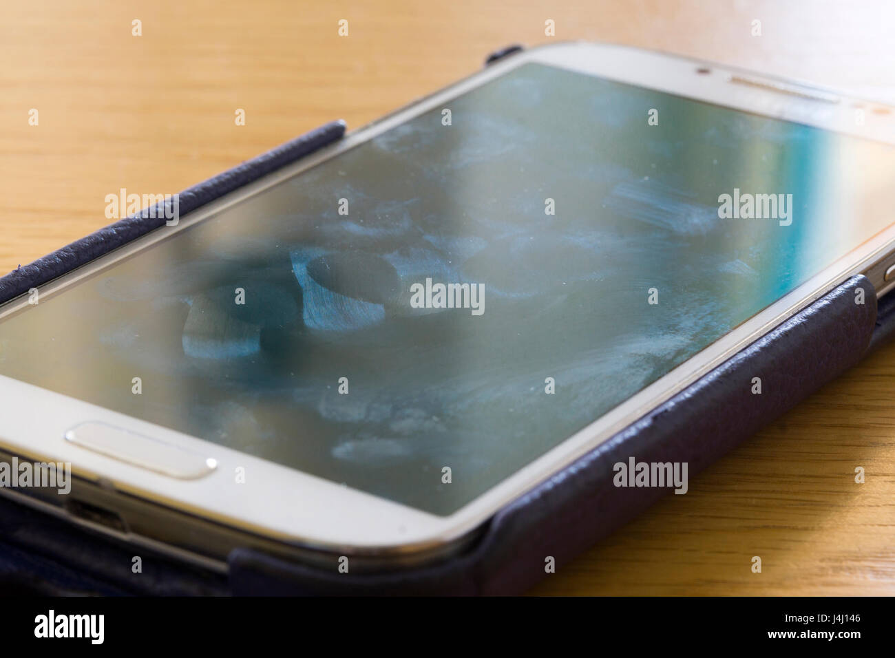 A closeup on a smartscreen screen showing smears and fingerprints - Stock Image