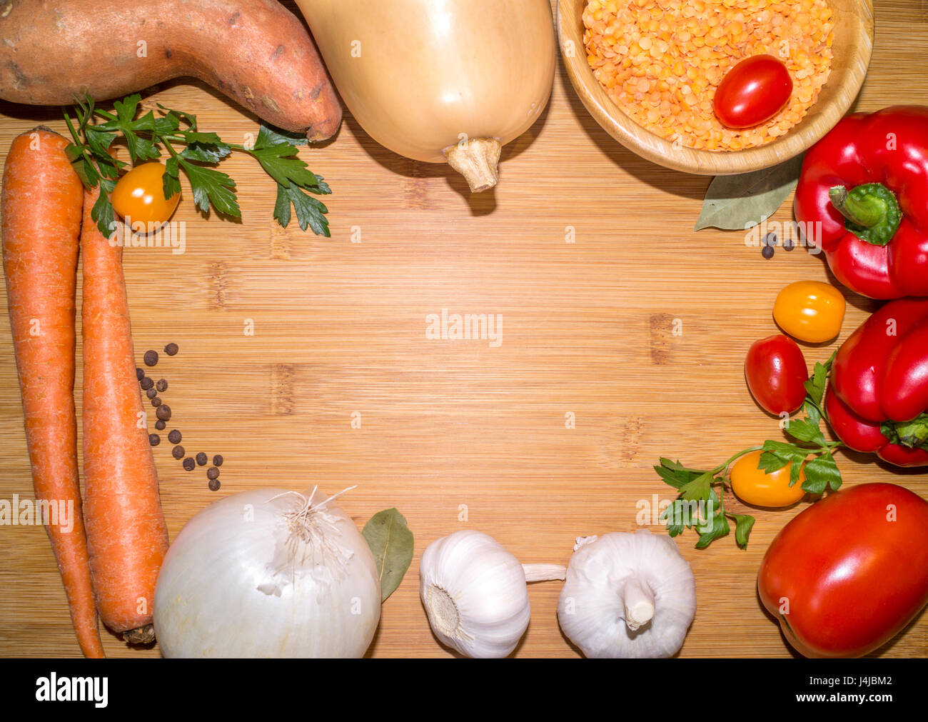 ingredients for lentil soup on a wooden board with copy space in the center Stock Photo