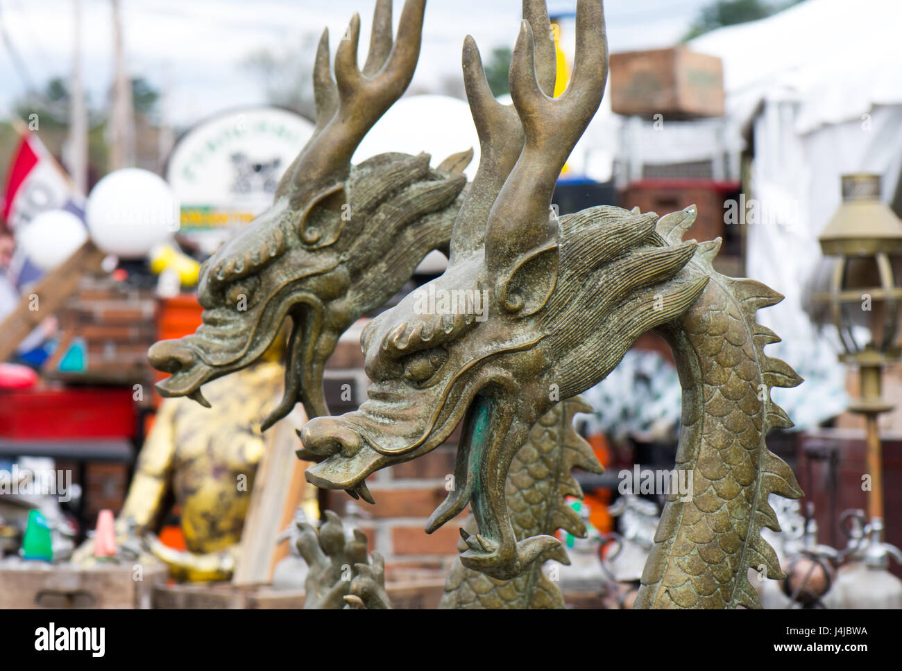 A pair of Asian dragon statues at an outdoor antique fair. - Stock Image
