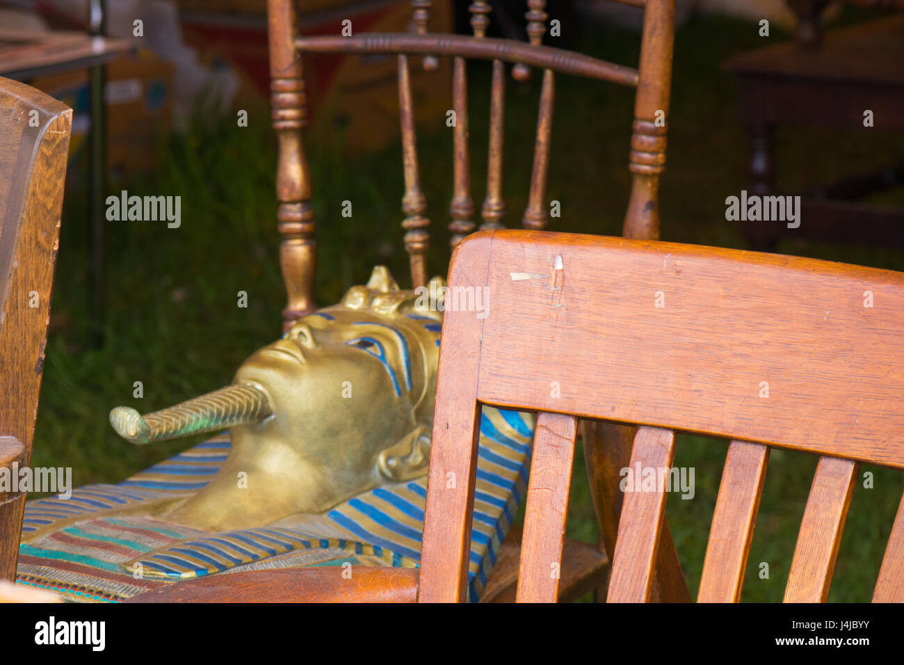 King Tut mask rests on antique chairs at flea market. - Stock Image