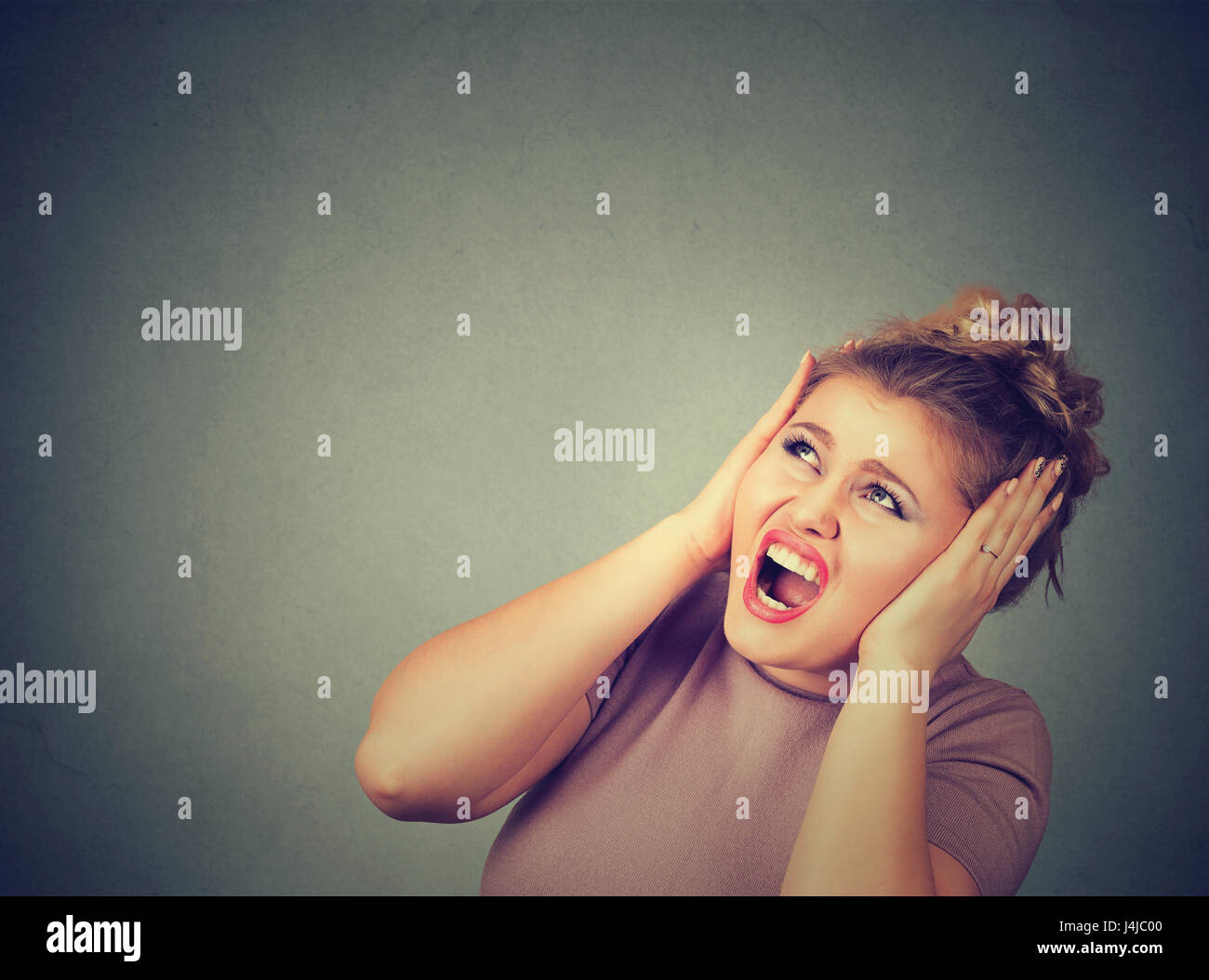 Stressed frustrated woman covering her ears with hands. - Stock Image