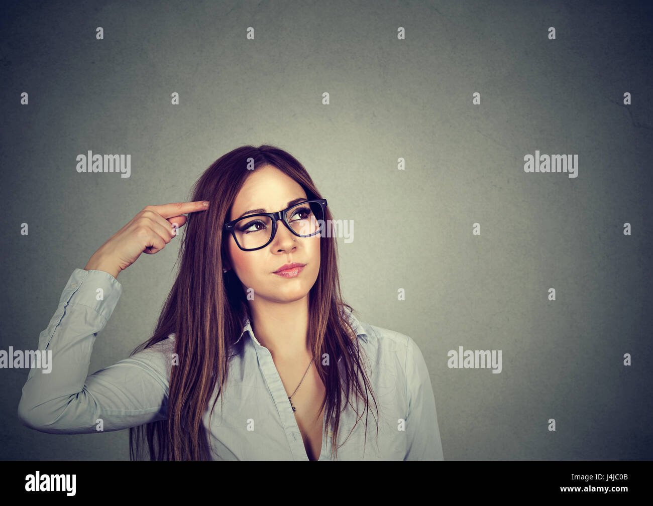 Portrait confused thinking young woman bewildered scratching head seeks a solution looking up isolated on gray wall - Stock Image