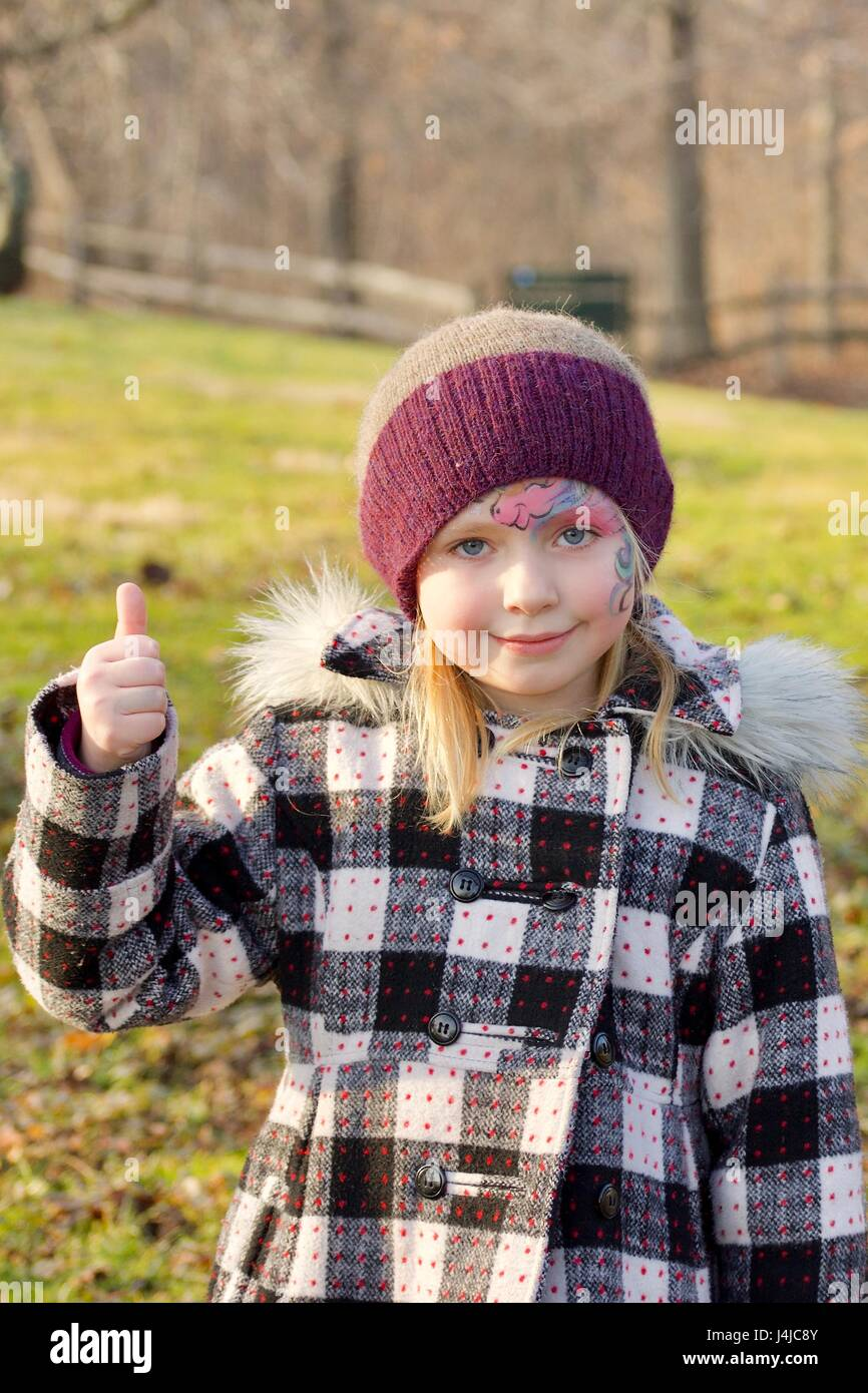 adorable school age girl giving thumbs up wearing face paint outside in autumn - Stock Image