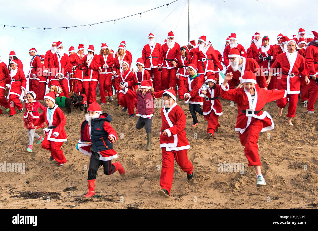 Perranporth, Cornwall, UK. 18th December 2016. Santa's on the sand an annual charity run on Perranporth beach in - Stock Image