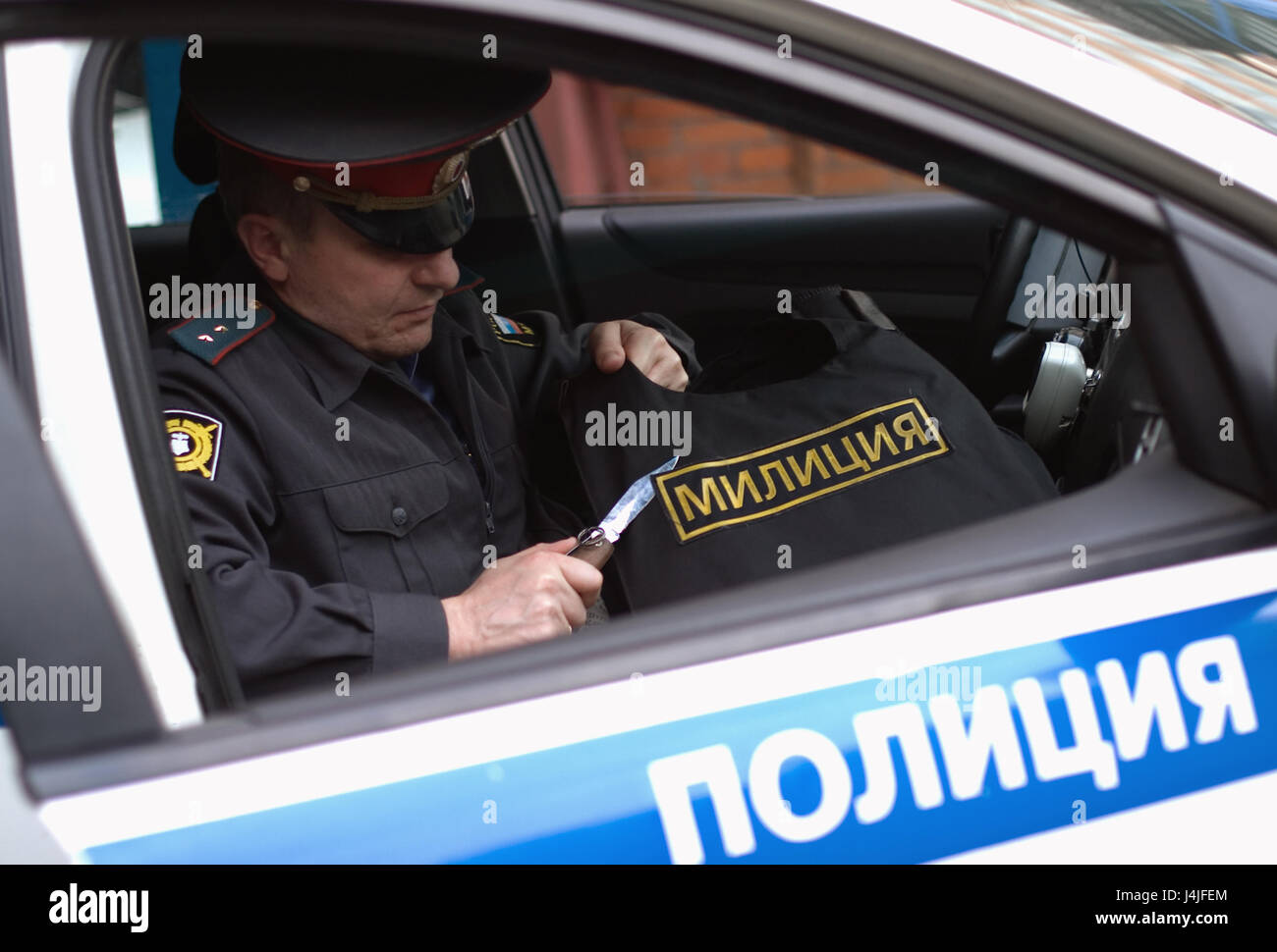Moscow, Russia, May 19, 2012: A Russian policeman cuts off a 'police' badge from bulletproof vest. - Stock Image