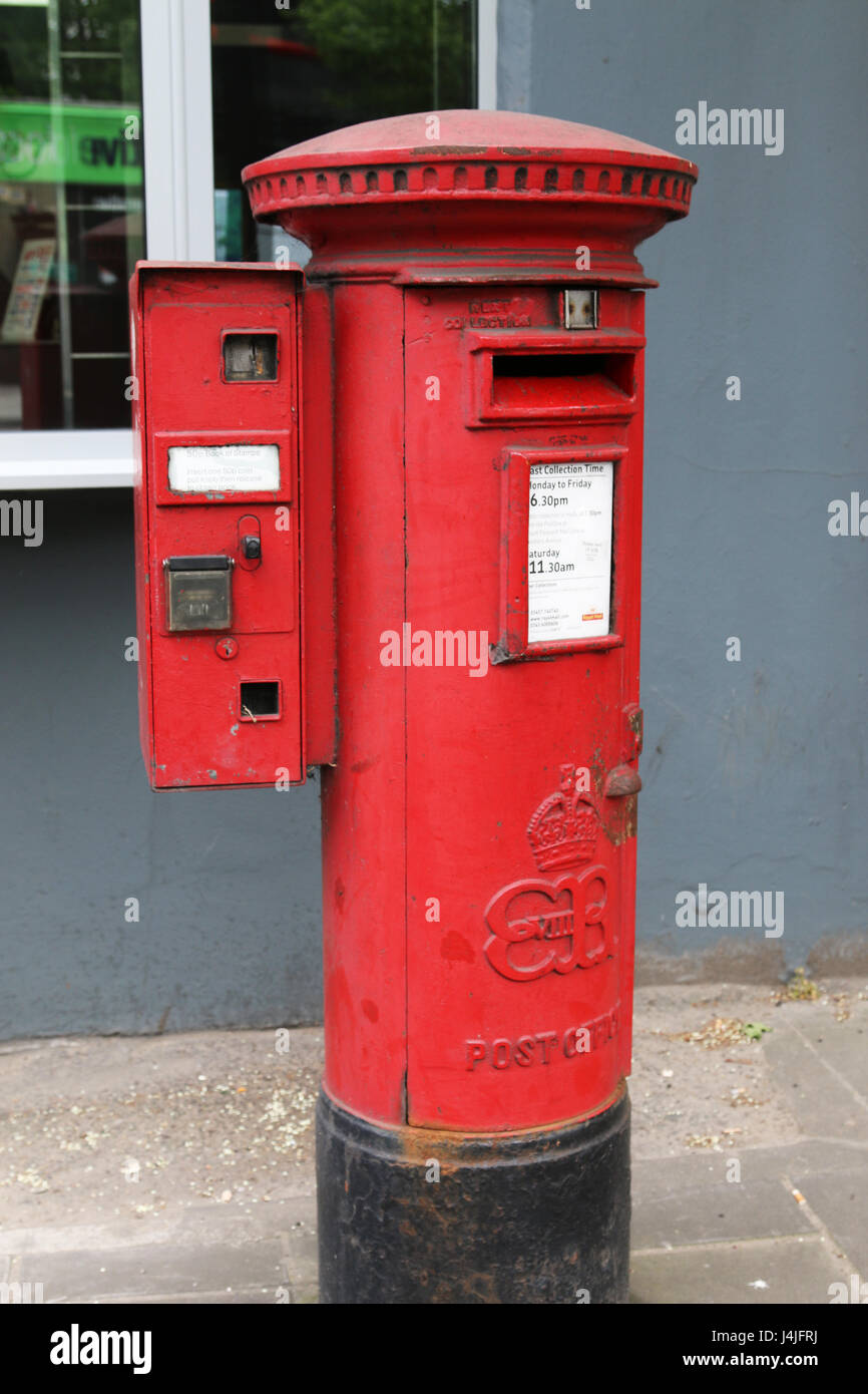 Red postbox on street - Stock Image