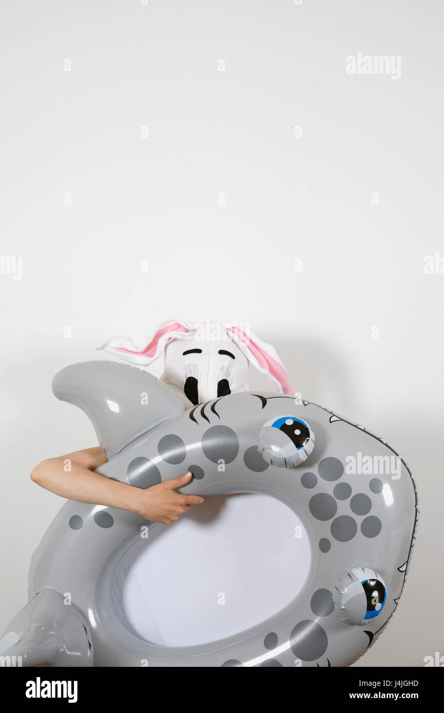 Rabbit woman playing and hiding behind an inflatable shark - Stock Image