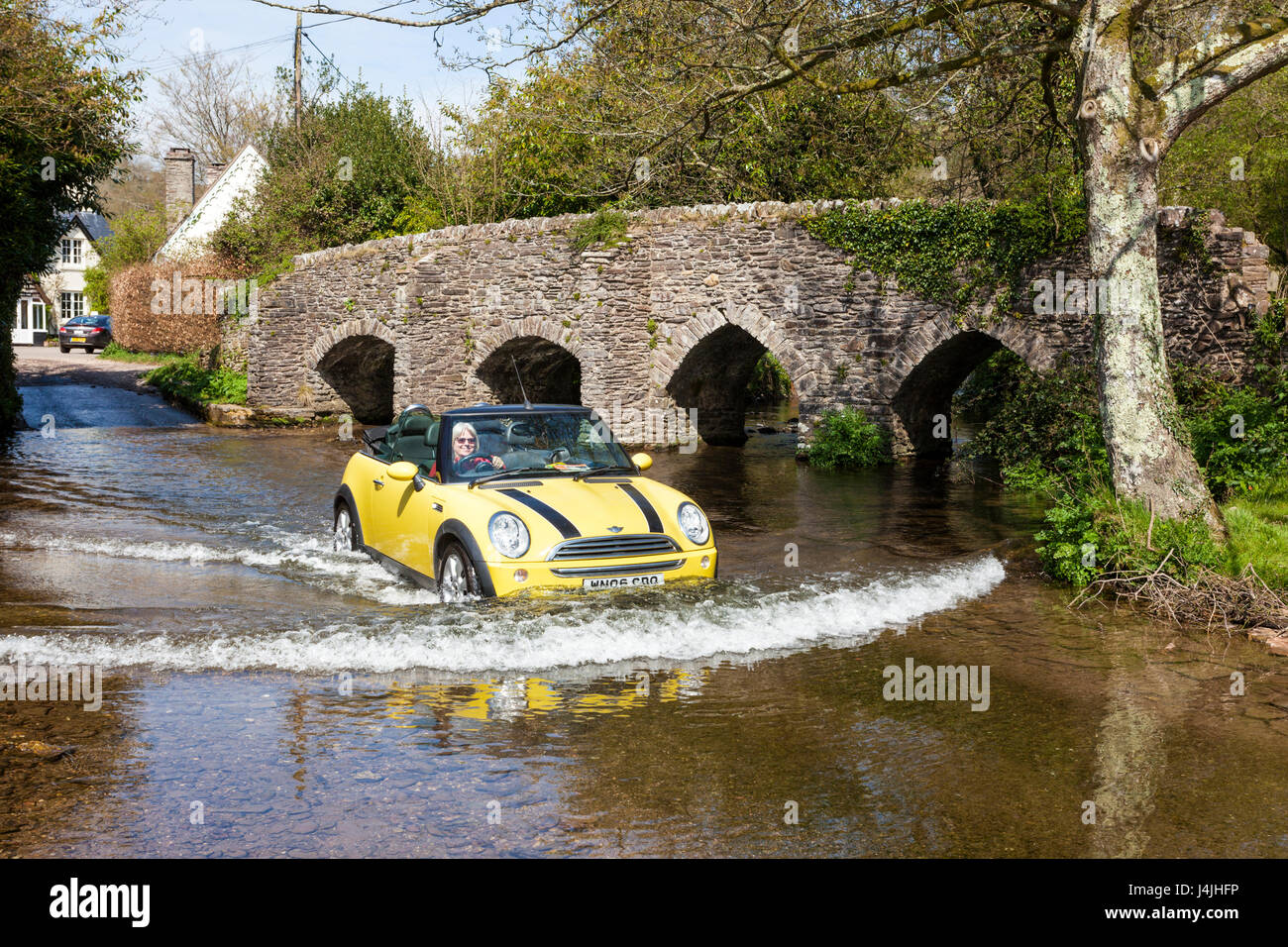 A smiling woman driving a convertible Mini Cooper through the ford beside the medieval packhorse bridge crossing - Stock Image