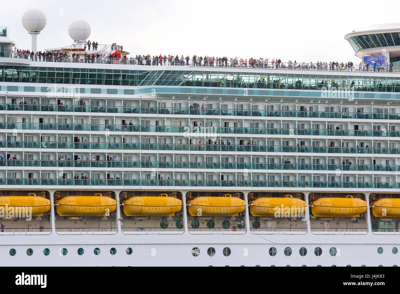 Passengers stand atop Royal Caribbean's MS Navigator of the Seas as it departs Southampton - Stock Image