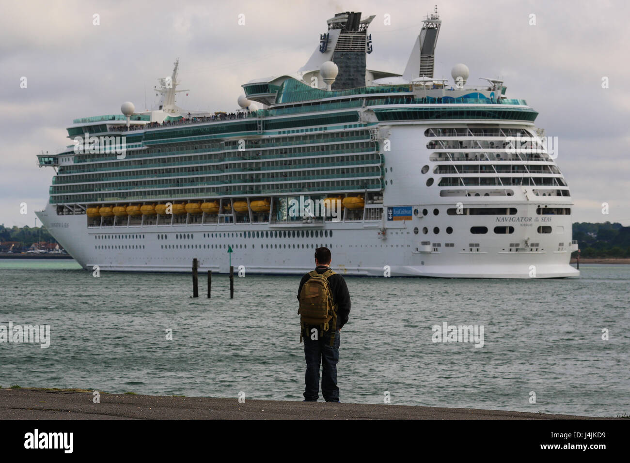 A person watches on at Royal Caribbean's MS Navigator of the Seas departs Southampton Port. - Stock Image
