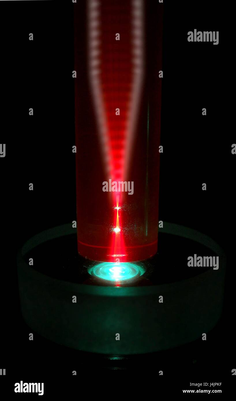 Laser and ruby rod. Experiment with a green laser beam being used to induce red luminescence in a rod of artificial - Stock Image