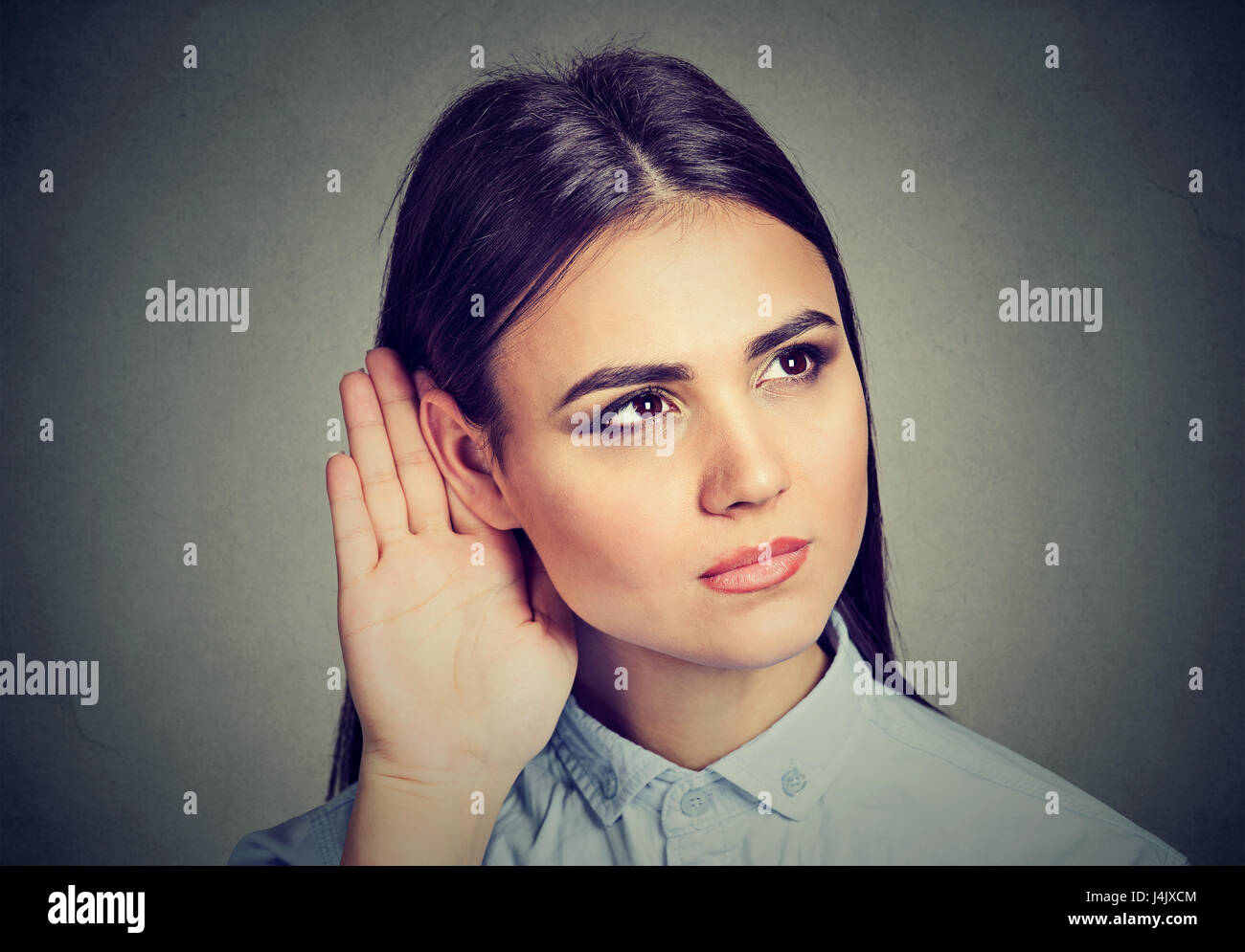 Woman with hand to ear gesture listening carefully - Stock Image