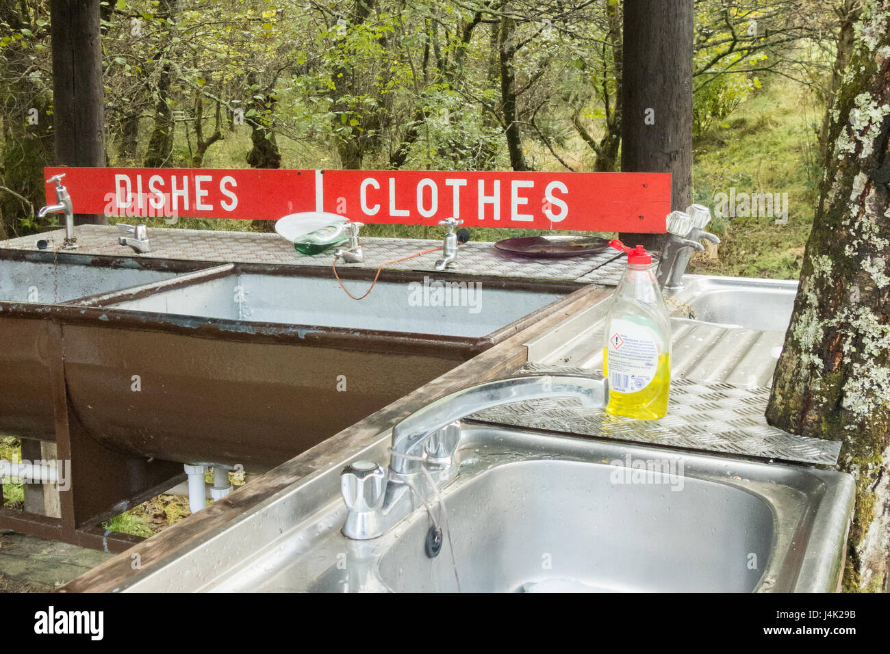 washing dishes and clothes by hand - small basic campsite washing up facilities - Red Squirrel campsite, Glencoe, - Stock Image