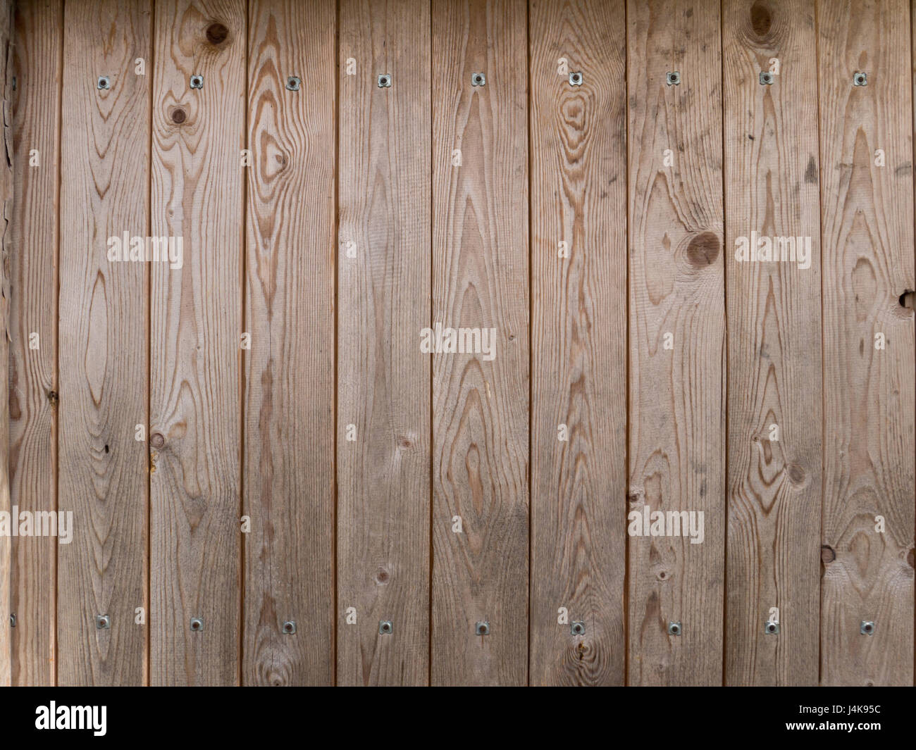 Wooden brown planks with metallic rivets background - Stock Image