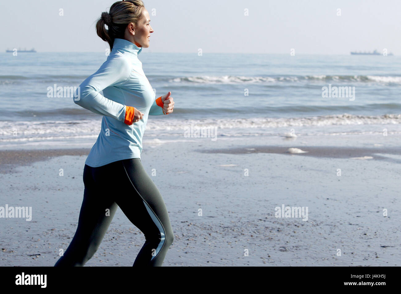 Beach, jogger, preview, detail, autumn 30-40 years, winter clothes, woman, jogging, jog, running, fitness, training, - Stock Image