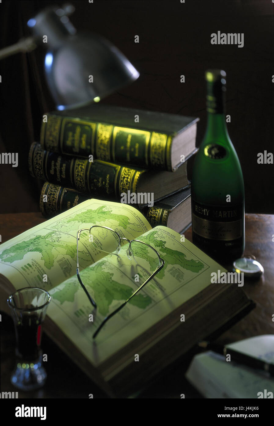 Table, cognac flask, books, encyclopaedia, maps, reading glasses still life, object photography, icon, read, learn, - Stock Image