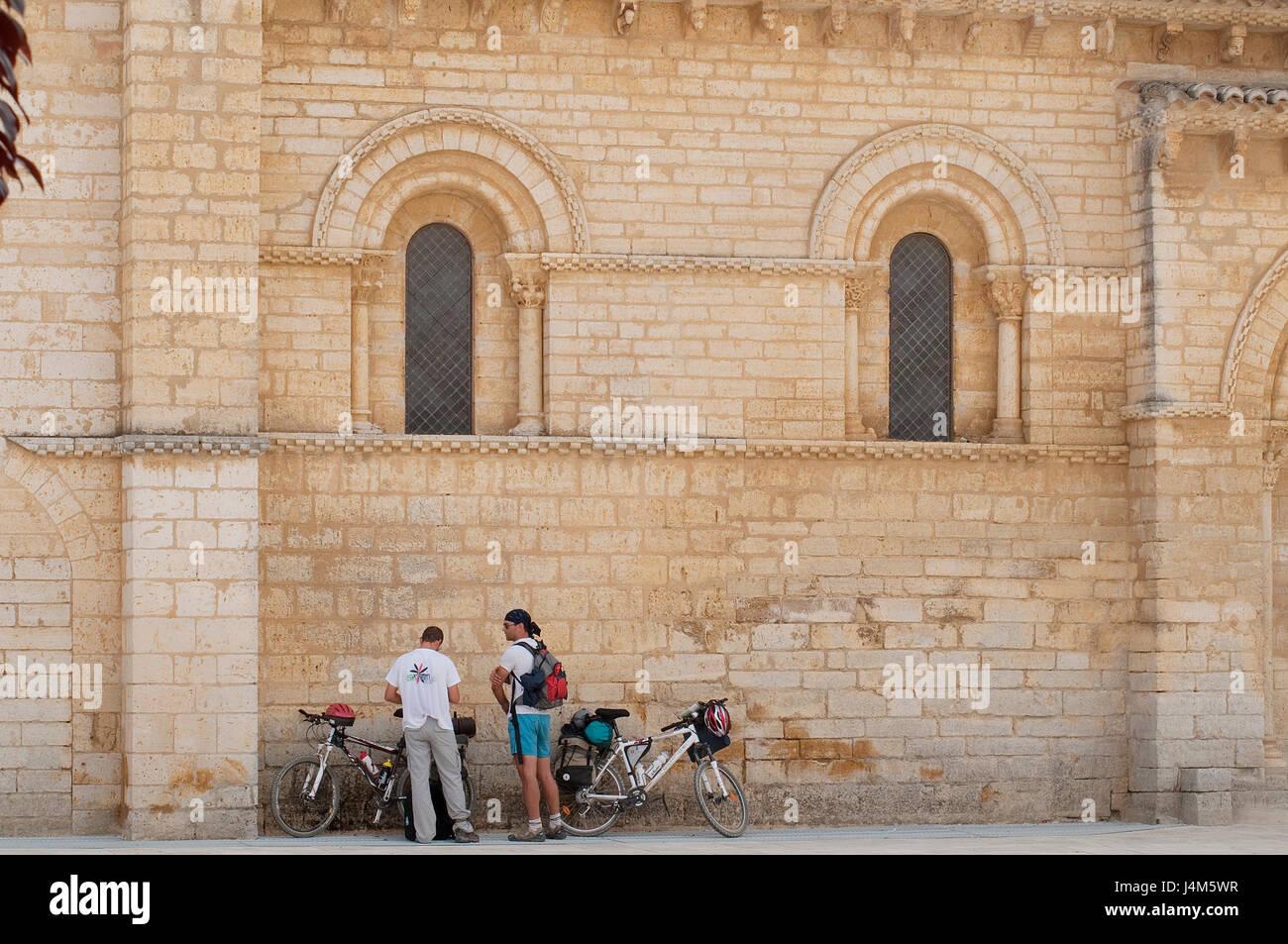 Two pilgrims at San Martin church. Camino de Santiago, Fromista, Palencia province, Castilla Leon, Spain. - Stock Image
