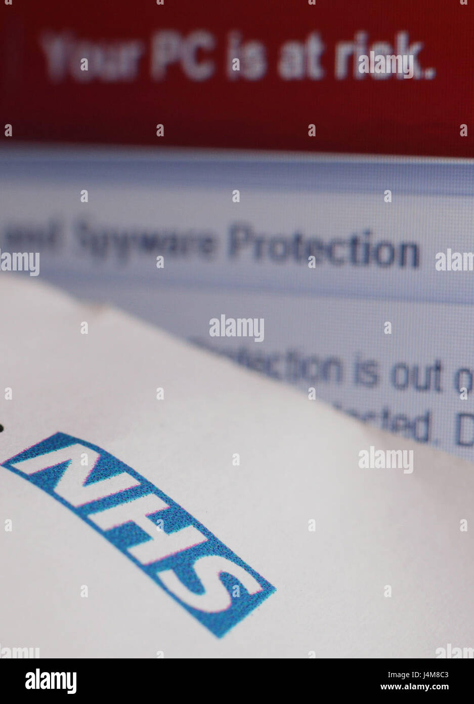 A patient appointment letter from an NHS hospital, next to a virus and spyware warning message on a laptop screen - Stock Image