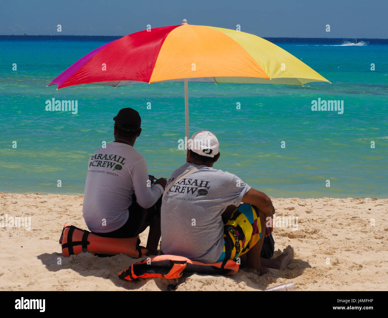 Beach vendors sheltering beneath beach brolly - Stock Image
