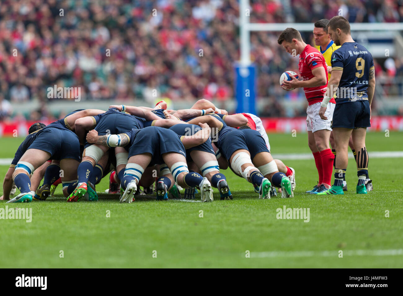 A rugby scrum is ready for the scrum half to put the ball in - Stock Image