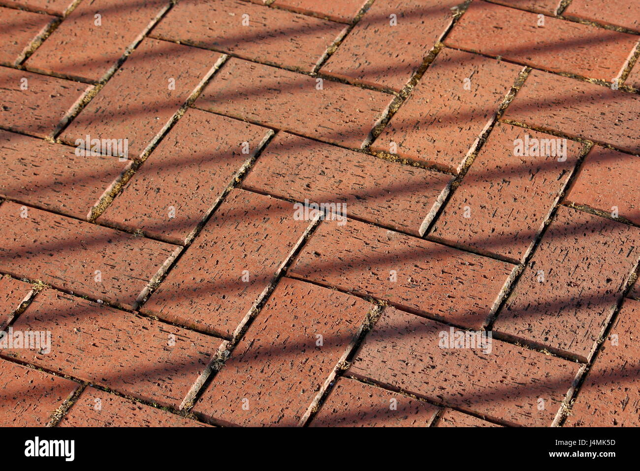 Red Brick Paving Floor Texture Herringbone Design Pattern With Diagonal Lines Of Fence Shadow