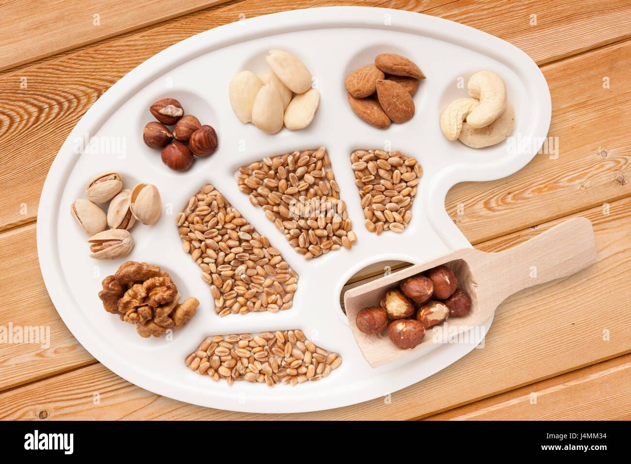 Verschiedene Nüsse, Mandeln und Getreidekörner auf weißer Maler-Pallette freigestellt auf schrägen Fichten-Brettern. Stock Photo