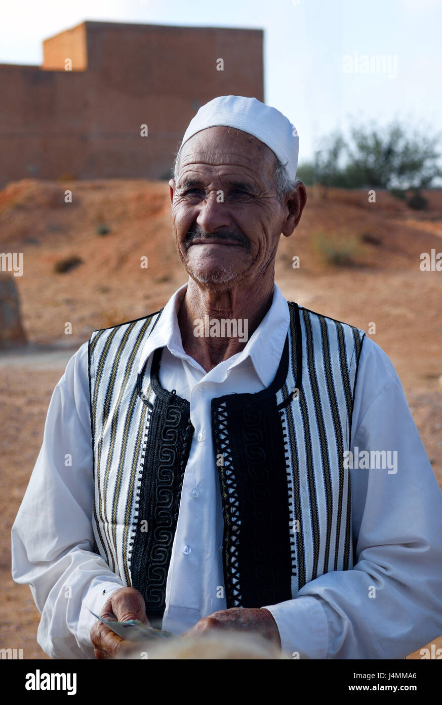 GHARJAN, LIBYA SEPT 27, 2009: Libya; An elderly Libyan vendor in traditional clothes near the entrance to the traditional - Stock Image