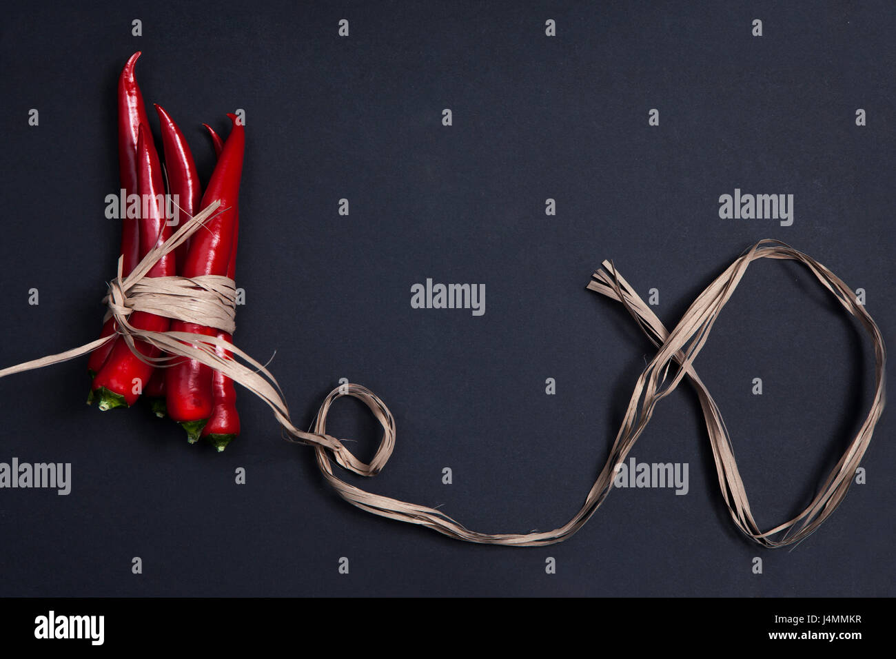 Postcards for recipes. Red chile pepper, tied with twine, on a gray napkin. Copy space - Stock Image