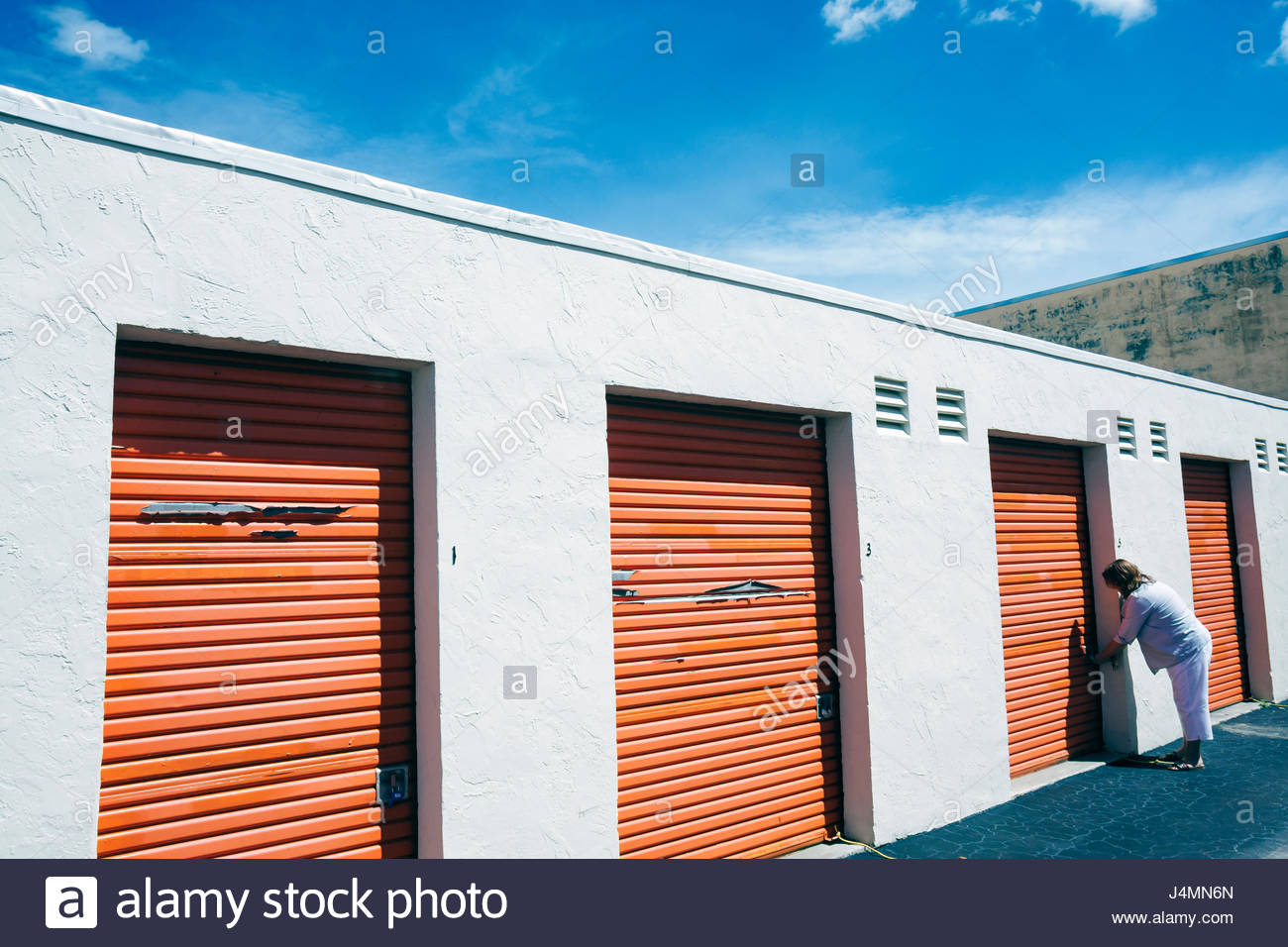 Miami Hialeah Florida Public Storage Business Self Storage Unit Locker  Rental Mini Warehouse Woman Unlocking Orange Door