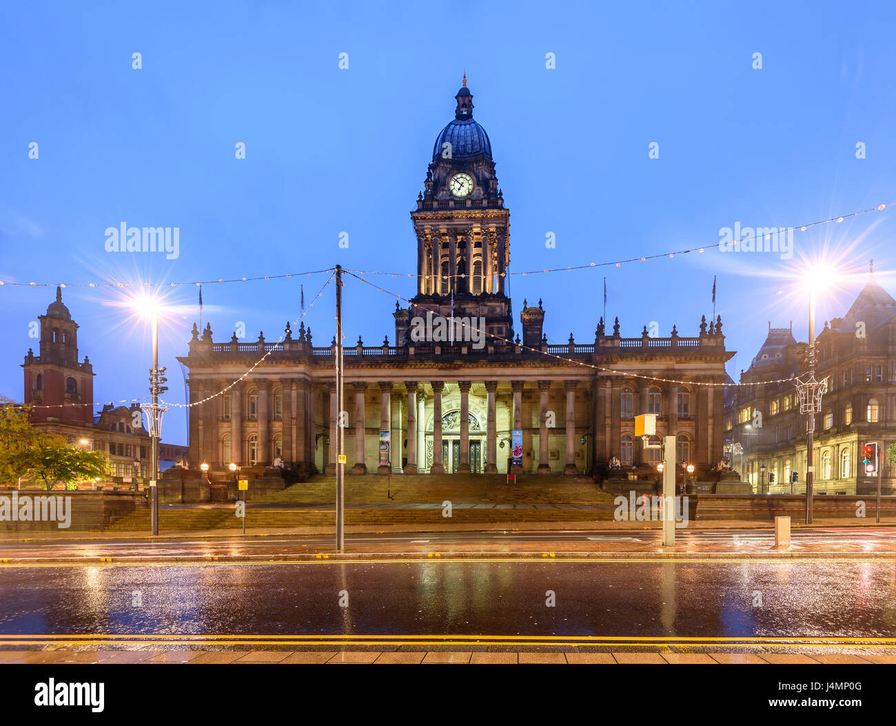 Wet road passing in front of Leeds Town Hall - Stock Image