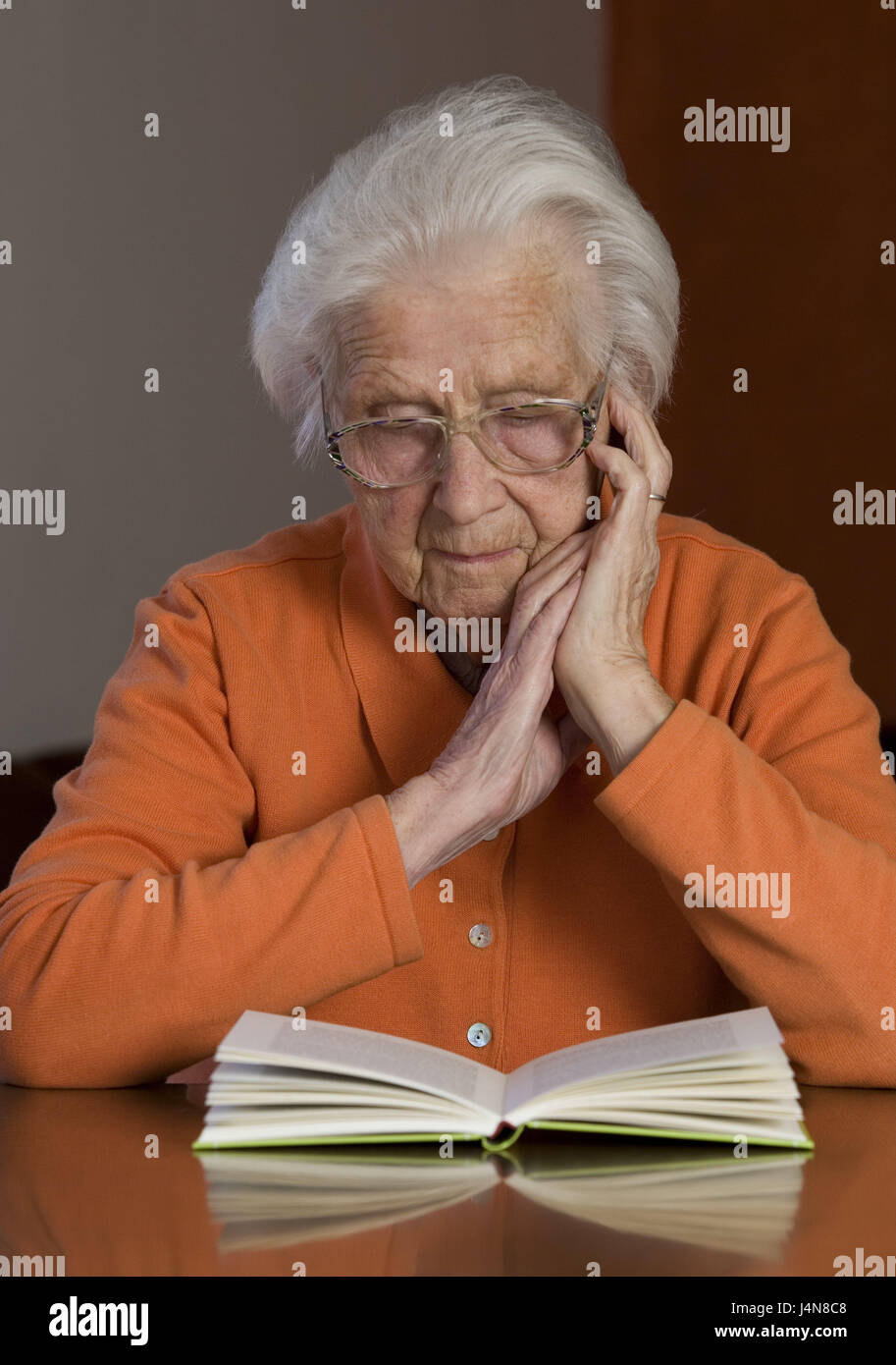 Senior, table, sit, read book, concentration, person, pensioner, woman, glasses, view, leisure time, hobby, activity, - Stock Image