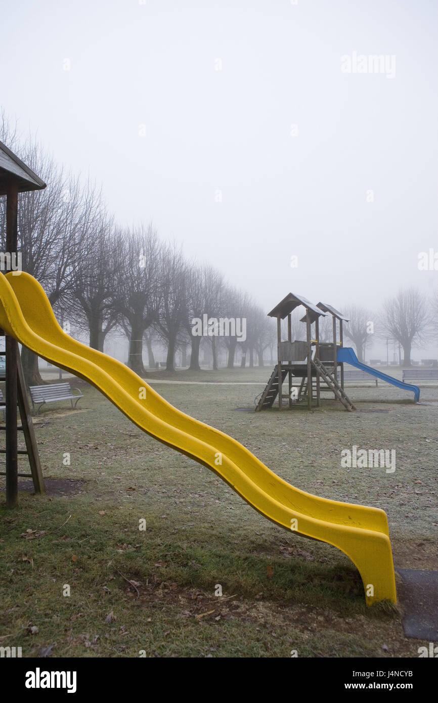 Children's playground, wooden tower, children's slides, fog, deserted, playground, plastic children's - Stock Image