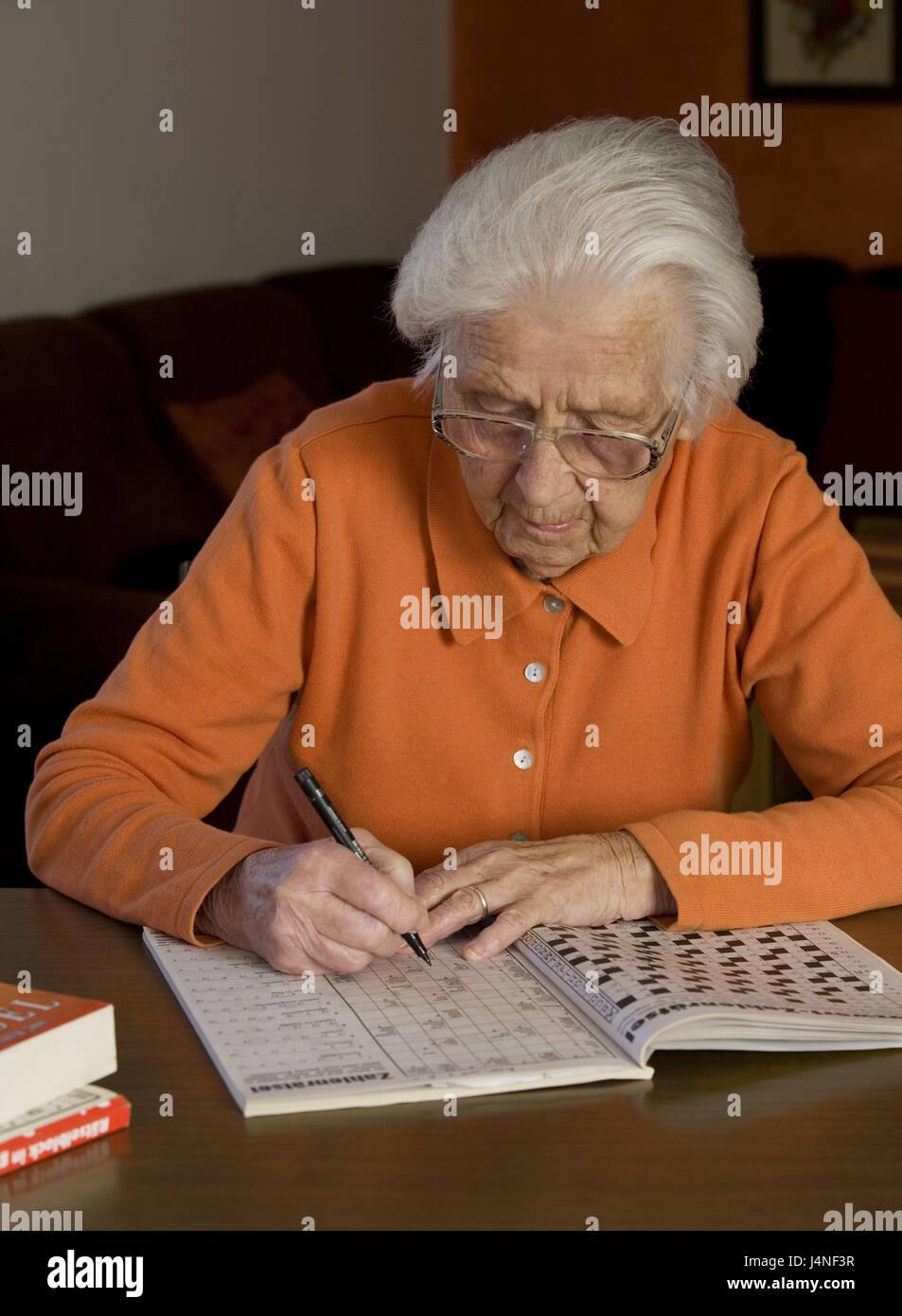 Senior, table, sit, write crossword puzzle, concentration, portrait, woman, person, glasses, view, puzzle book, - Stock Image