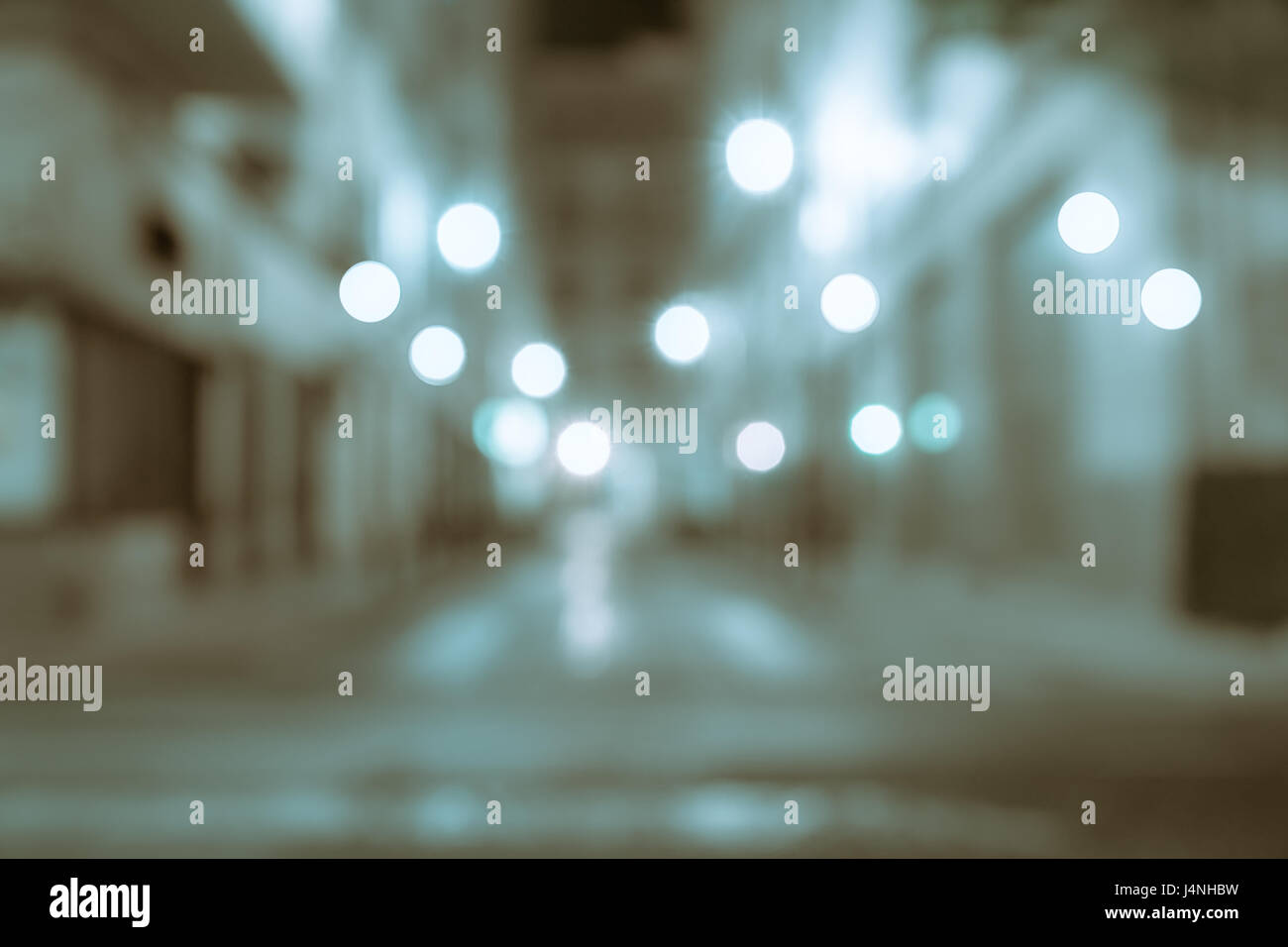 Background blue and brown tones retro effect lights in gritty urban street abstract street between buildings at - Stock Image