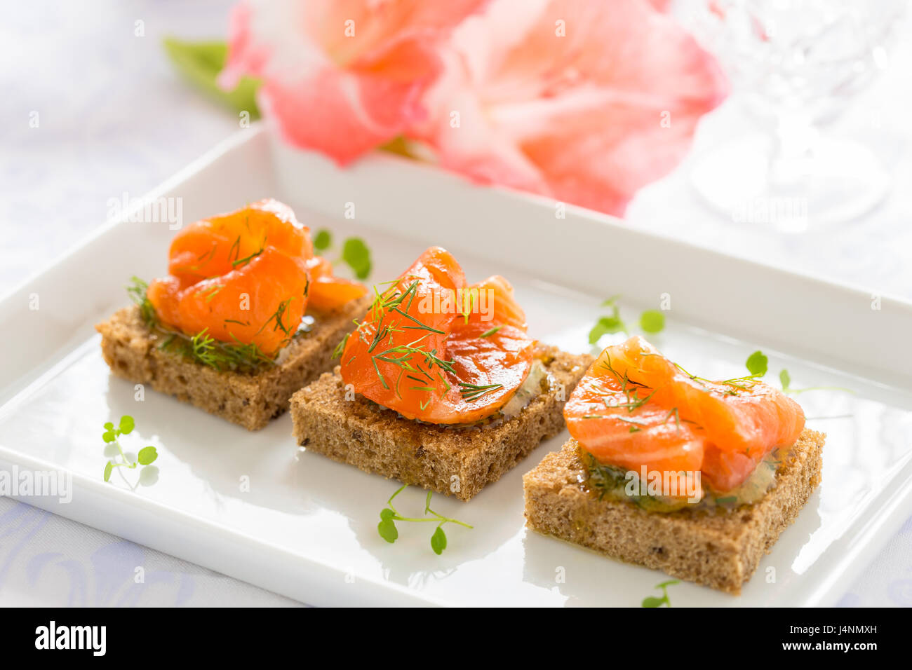 Delicious appetizer canapes of black bread with smoked salmon for holiday - Stock Image