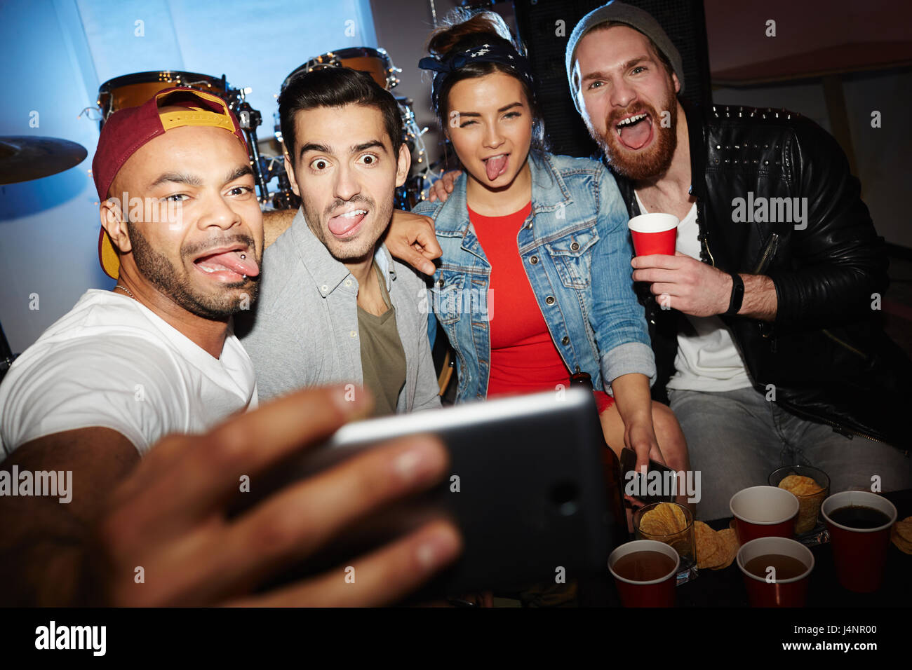 Group of modern young people chilling at night club party, posing for selfie photo, grimacing and having fun - Stock Image