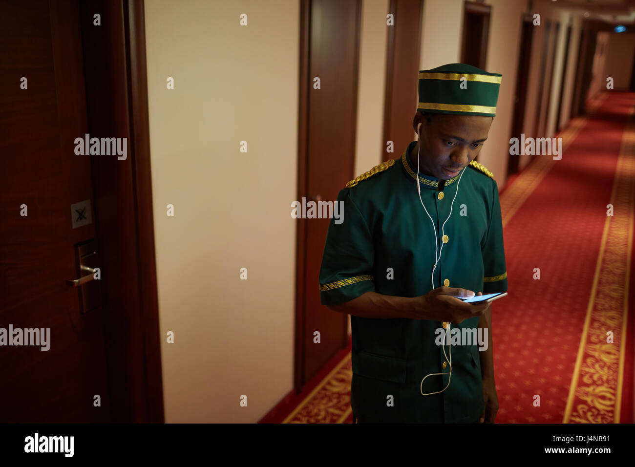 Portrait of African-American bellboy listening to music in hall of hotel, on break from work - Stock Image