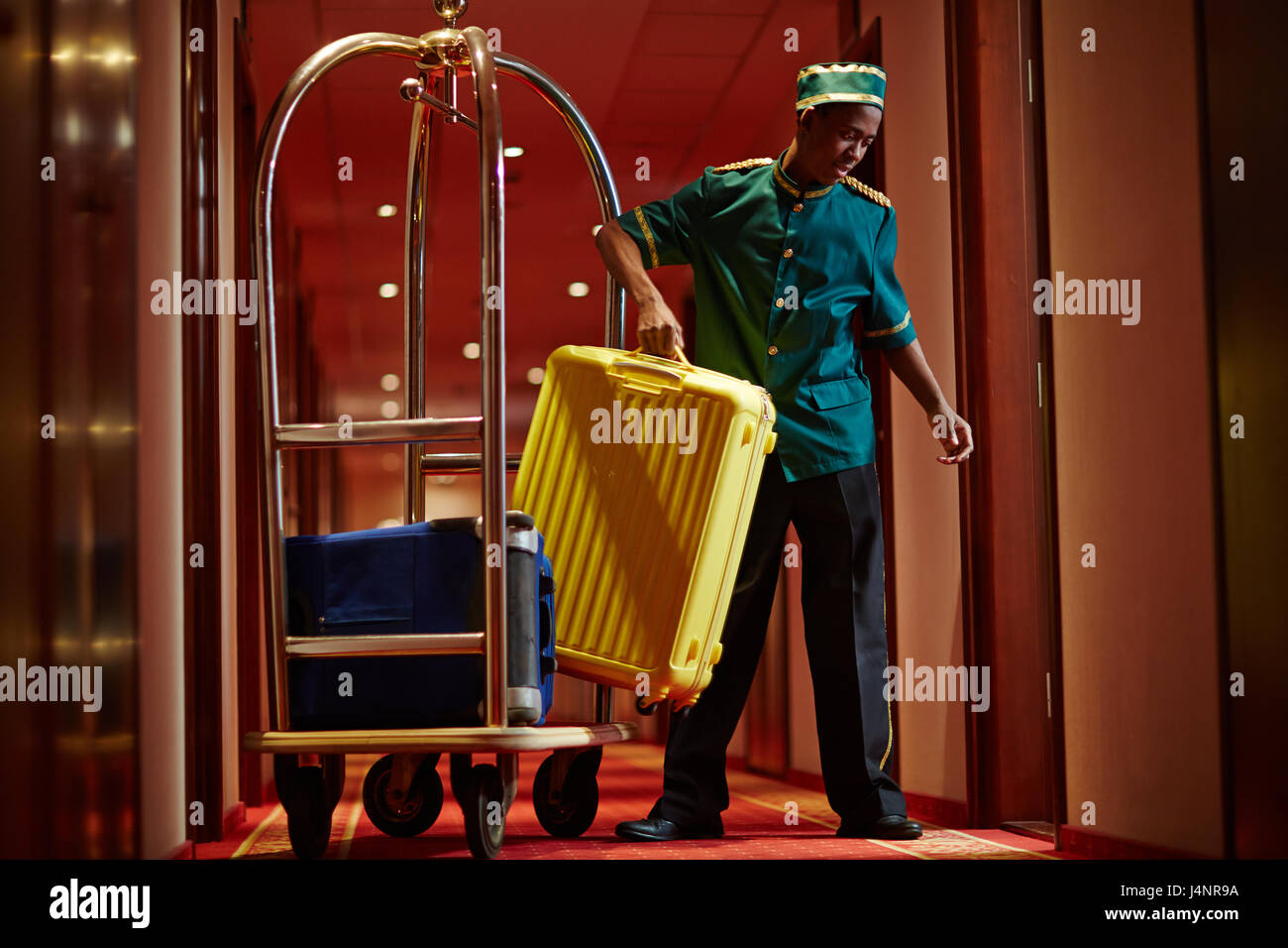 Portrait of African bellboy with luggage cart in hotel hallway, bringing bags to guest rooms - Stock Image