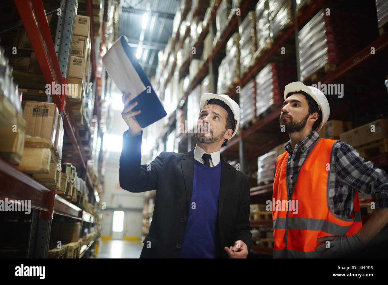 Two supervisors discussing amount of goods for export on shelves of warehouse - Stock Image