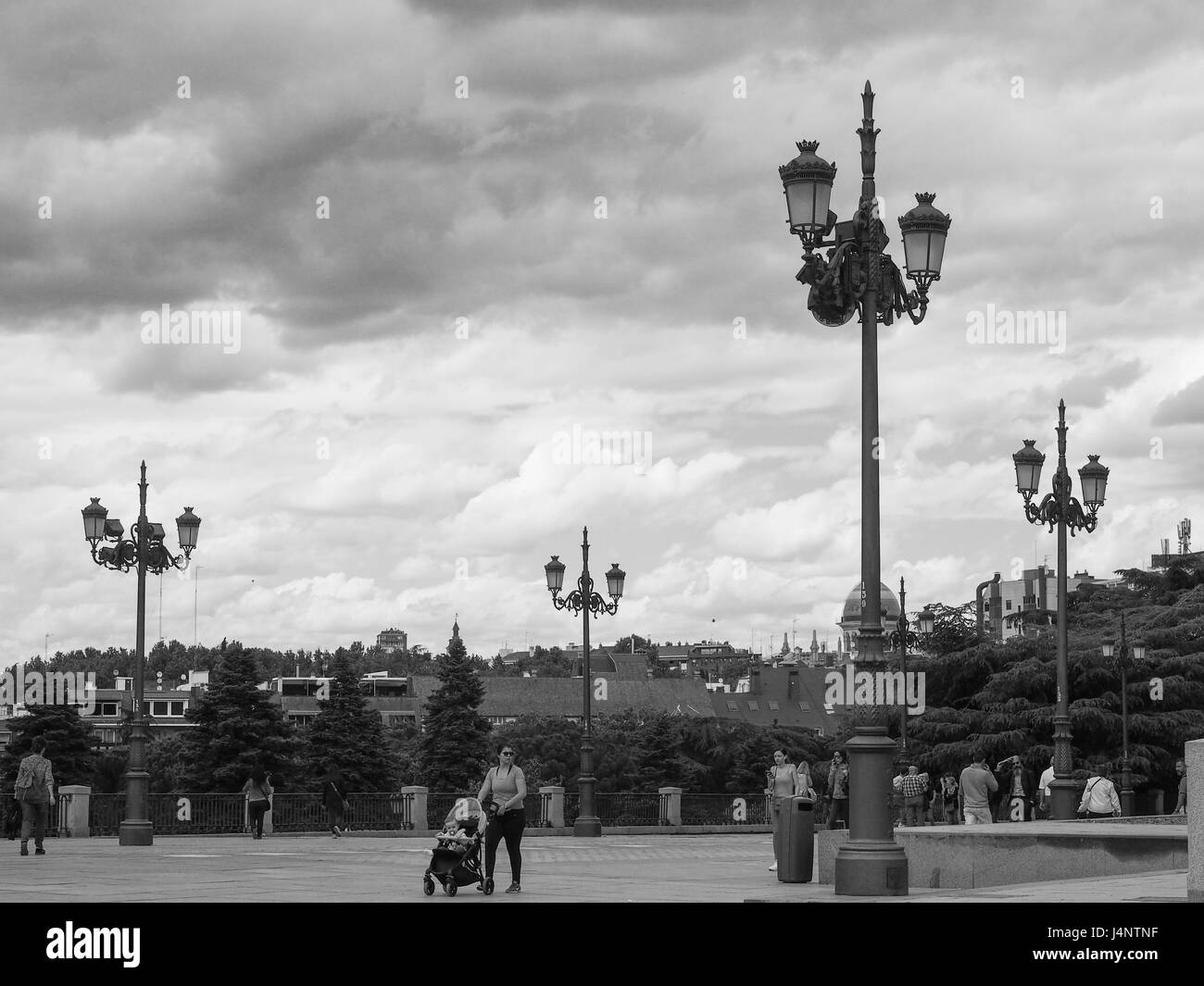 a black and white view of Street light lights lamposts lamps piercing the cloudy sky in the Jardines del Cabo Noval - Stock Image